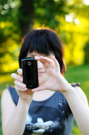 Young woman taking photo using her mobile phone