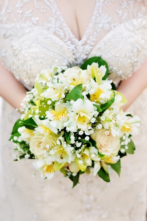 Bride holding beautiful yellow wedding flowers bouquet