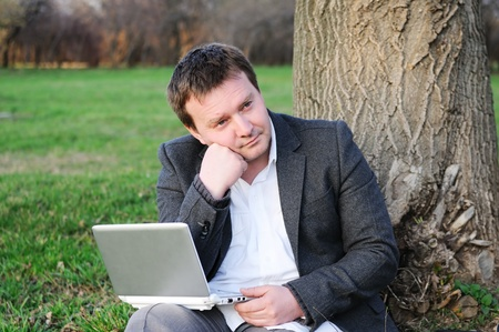 Businessman with laptop working under a tree Stock Photo