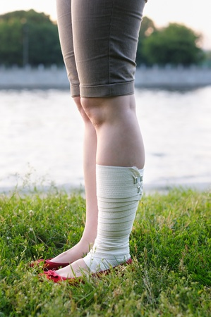 ankle strap: A woman with elastic bandage on injured leg Stock Photo