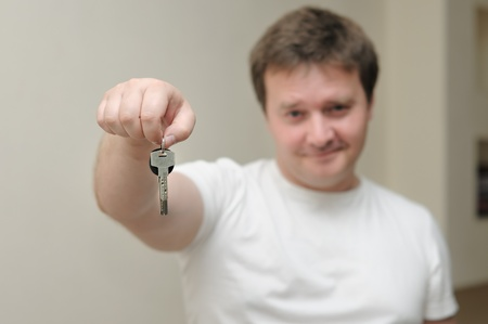 Portrait of a cute man holding the keys of his home, focus is on the keys photo