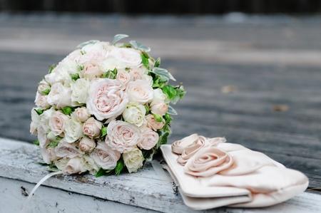Beautiful pink wedding flowers bouquet and bride handbag photo