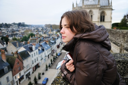 Portrait of young woman looking on small town (France, Amboise) Stock Photo