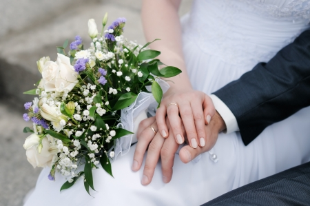 Bride and grooms hands with wedding rings and bouquet of flowers photo