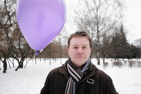 Funny man holding purple balloon Stock Photo - 10093445
