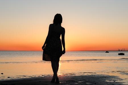 Portret van jonge vrouw als silhouet door de zee