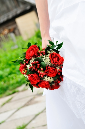 arm bouquet: Bride holding beautiful red wedding flowers bouquet  Stock Photo