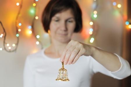 handbell: Woman holding a golden handbell