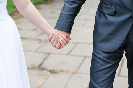 Bride and groom holding each others hands  photo