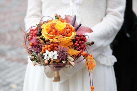 아름 다운 오렌지 결혼식 꽃 꽃다발을 들고하는 신부