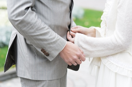 fasten: Bride adjusting or fasten grooms suit