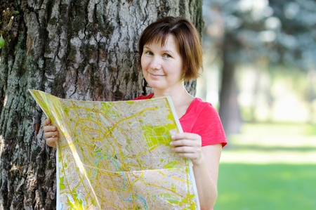 Attractive woman with map under a tree  photo