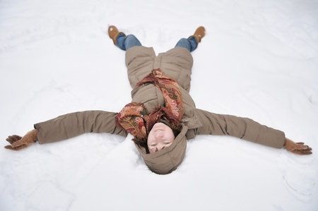 Winter fun - snow angel - happy woman playing in snow  photo