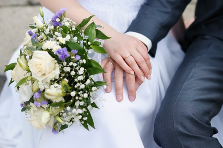 Bride and groom's hands with wedding rings holding wedding bouquet Stock Photo - 12204916