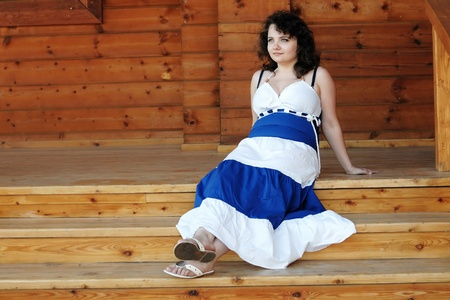 curly headed: Frizzy woman sitting on wooden porch