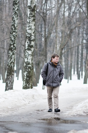 winter thaw: Middle age man walking in spring park