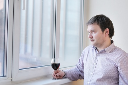 grievous: Middle age man with wine glass looking into the window Stock Photo