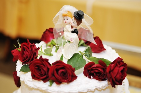 Figurines on top of wedding cake with real roses decorations Stock Photo - 12867660