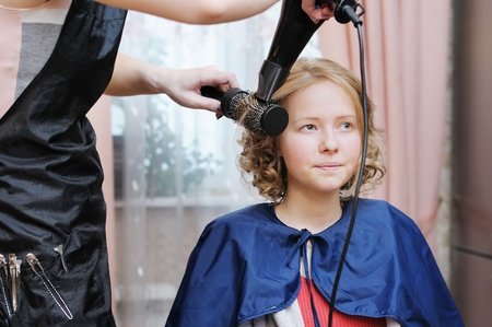 curly headed: Stylist making a fancy hairstyle  Stock Photo