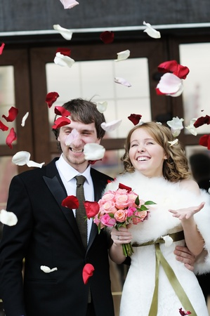 wedlock: Just married couple under a rain of rose petals