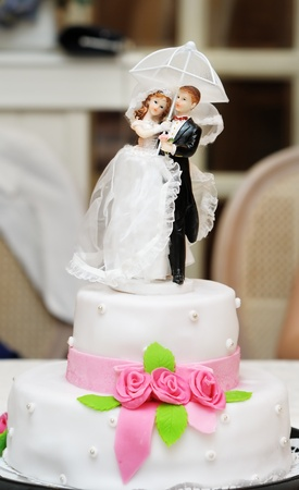Figurines on top of wedding cake with roses decorations Stock Photo