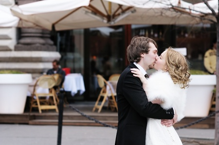 Bride and groom kissing outdoors photo