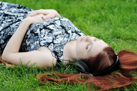 Pensive young woman lying on grass listening to music outdoors photo