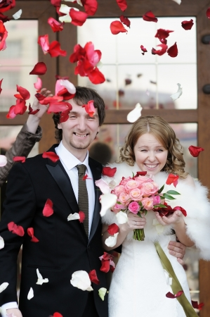 Just married couple under a rain of rose petals photo