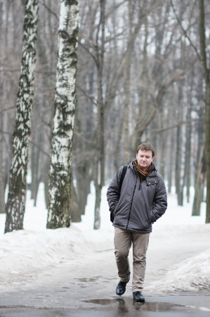 Middle age man walking in snow park photo