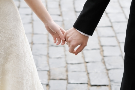 Bride and groom holding hands outdoors photo