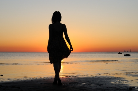 woman shadow: Portrait of young woman as silhouette by the sea Stock Photo