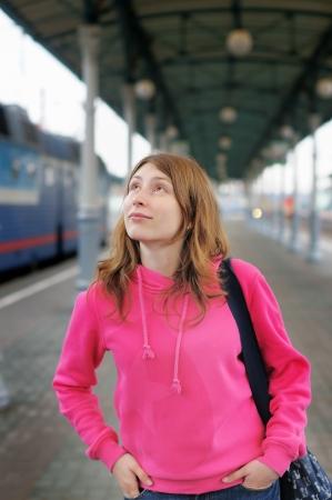 parting off: Girl waiting train on railway station platform