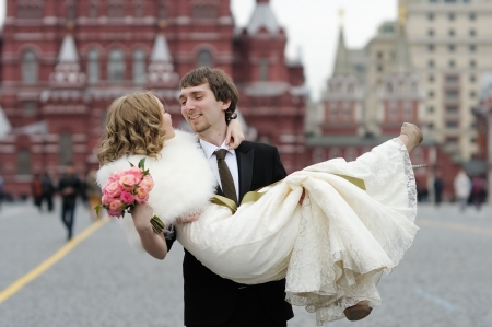 Happy groom holding young beautiful bride in his arms