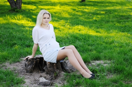 Beautiful young pregnant woman in park photo