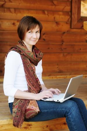 old technology: Donna seduta con computer portatile sul portico in legno Archivio Fotografico