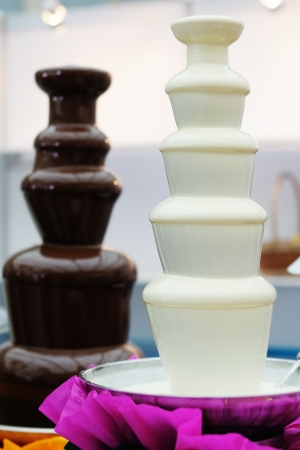 Delicious chocolate fondue fountains on a table Stock Photo