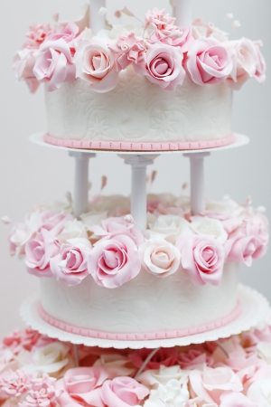 Delicious white wedding cake decorated with pink cream roses Stock Photo - 19425211