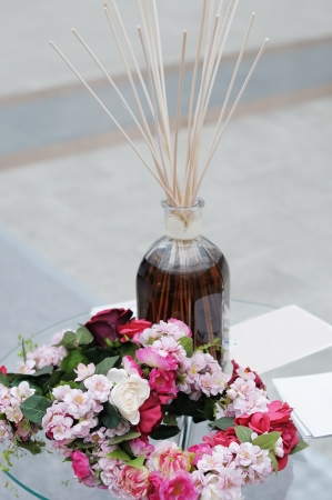 air diffuser: Aroma diffuser with bamboo sticks mounted and wreath of flowers, focus on wreath