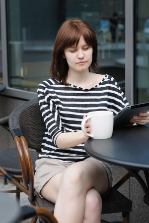 Girl drinking coffee and using tablet computer in a outdoor cafe photo