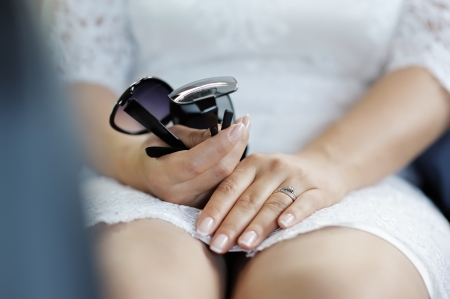 Brides hands holding sunglasses, focus on rings photo