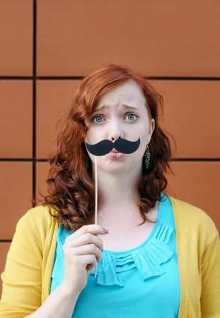 Funny young woman with mustache party accessory