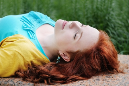 Beautiful young woman lying with close eyes Stock Photo - 20879180
