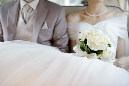 White wedding flowers bouquet on wedding dress Foto de archivo