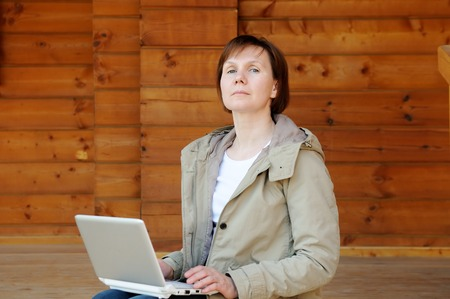 Haughty woman with laptop sitting on wooden porch Stock Photo - 26550938