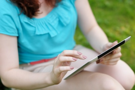 earnestly: Young woman using tablet computer outdoors Stock Photo