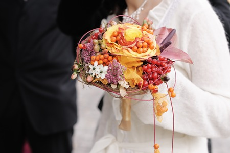 Bride holding beautiful orange wedding flowers bouquet photo