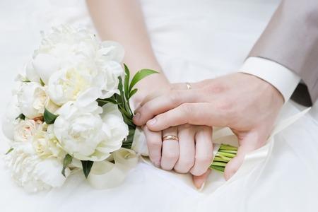 Handen van de bruid en de bruidegom met trouw ringen