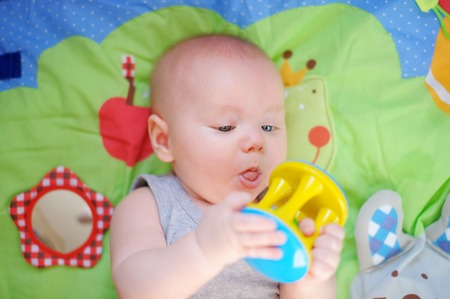 Four month old baby play with bright toy photo