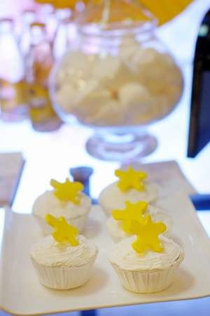 Delicious white weddings or birthdays cupcakes on sweet table photo