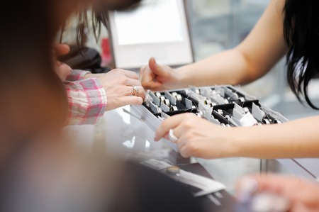 Woman trying wedding rings at a jeweller, focus on hand photo